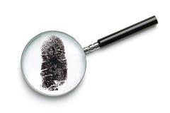 Vergrootglas dat vingerafdruk onderzoekt Stock Fotografie