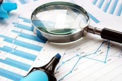 Vergrootglas en financiële documenten Controle en boekhouding royalty-vrije stock afbeelding