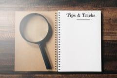 Vergrootglas en notitieboekje met UITEINDEN EN TRUCSwoord met exemplaarruimte op houten lijst stock fotografie
