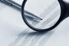 Vergrootglas en pen over financieel rapport Stock Afbeelding
