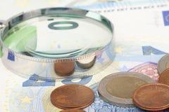 Vergrootglas en vele euro rekeningen en coins Limited velddiepte royalty-vrije stock afbeelding