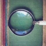 Vergrootglas met oude Boeken op Uitstekende Achtergrond met Insta Stock Foto's