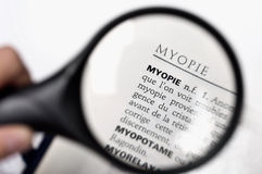 Vergrootglas op het woord myopie (bijziendheid) stock fotografie