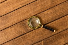Vergrootglas op houten lijst Het concept van het onderzoek stock afbeeldingen
