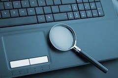 Vergrootglas op laptop Royalty-vrije Stock Afbeeldingen