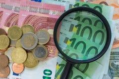 Vergrootglas op stapel van Euro bankbiljetten met Euro muntstukken als FI royalty-vrije stock afbeelding