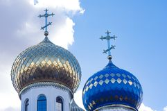 Vergulde en blauwe koepel van een kerk met kruisen, tegen een blauwe hemelachtergrond royalty-vrije stock foto