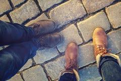 Verhältnis in einem Paar Liebhabern, Seite zwei vorbei Füße in den Schuhen auf den Pflastersteinen Lizenzfreie Stockfotografie