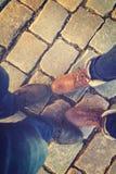 Verhältnis in einem Paar Liebhabern, zwei nebeneinander Füße in den Schuhen auf den Pflastersteinen Stockfoto