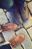 Verhältnis in einem Paar Liebhabern, zwei nebeneinander Füße in den Schuhen auf den Pflastersteinen Stockbilder