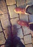 Verhältnis in einem Paar Liebhabern, zwei nebeneinander Füße in den Schuhen auf den Pflastersteinen Stockfotos