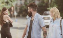 Verhältnis-Problem Mann, der seine Frau oder Freundin betrügt Bärtiger Mann, der anderes Mädchen betrachtet Hippie, der zwischen  lizenzfreies stockbild