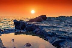 Verhärtete Lava und Ozean bei Sonnenuntergang stockfotografie