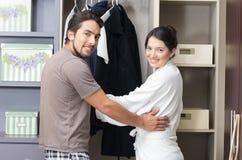 Verheiratete junge Paare, die im Wandschrank aufwerfen stockbild