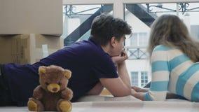 Verheiratetes Paar betrachtet das Fenster, das unter legt, auspacken Kästen nach Verlegung stock video
