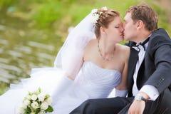 Verheiratetes Paar, das im Park küsst Stockbilder