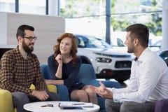Verheiratetes Paar, das mit einem Autohändler in einem Ausstellungsraum spricht lizenzfreie stockfotos
