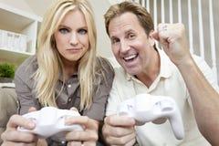 Verheiratetes Paar, das Spaß hat, Videospiel zu spielen Lizenzfreie Stockfotos