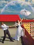 Verheiratetes Paar mit weißem Regenschirm auf dem Dach Lizenzfreies Stockbild