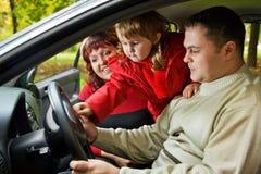 Verheiratetes Paar und kleines Mädchen sitzen im Auto im Park Stockfotos