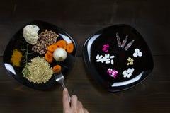 Verhinderung mit gesunder Ernährung oder Behandlung mit Medizin? Der Kontrast zwischen einer Platte voll des Gemüses und der Getr lizenzfreie stockfotos