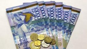 Verhoging van lonen, pensioenen, sociale betalingen en voordelen Papiergeld van de nominale waarde van tenge 10.000 en muntstukke stock foto's