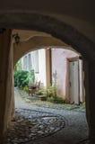 Verhoogde weg die in binnenplaats door passage leiden Stock Afbeeldingen