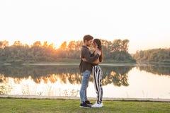 Verhouding, liefde en aardconcept - Aantrekkelijke vrouw en knappe man die en over waterachtergrond koesteren kussen stock foto