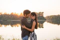 Verhouding, liefde en aardconcept - Aantrekkelijke vrouw en knappe man die en over waterachtergrond koesteren kussen stock fotografie