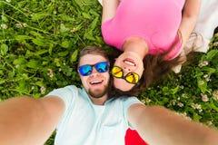 Verhouding, liefde en mensenconcept - gelukkig tienerpaar in op gras liggen en zonnebril die selfie overnemen stock afbeeldingen