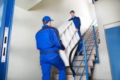 Verhuizers die Plank dragen terwijl thuis het Beklimmen van Stappen royalty-vrije stock afbeelding