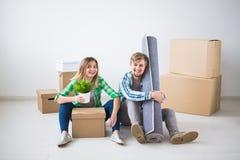Verhuizing, nieuw huis en onroerende goederenconcept - het Jonge paar upacking in hun nieuwe vlakte samen stock afbeelding