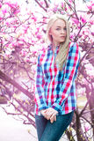 Verical portrait of modest young blonde girl with pink flowers Royalty Free Stock Image