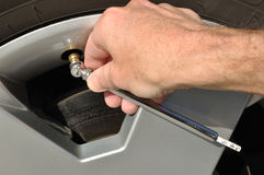 Verific a pressão de ar de um pneu Fotografia de Stock
