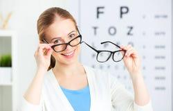 Verificação da visão a mulher escolhe vidros no oftalmologista o do doutor foto de stock royalty free