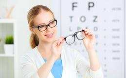 Verificação da visão a mulher escolhe vidros no oftalmologista o do doutor imagem de stock royalty free