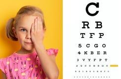 Verificação da visão olho da coberta uma da menina com mão Conceito da oftalmologia imagem de stock