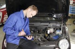 Verificação do mecânico mestre um carro Fotografia de Stock