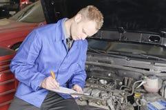 Verificação do mecânico mestre um carro Fotos de Stock