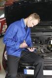 Verificação do mecânico mestre um carro Fotografia de Stock Royalty Free