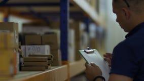 A verificação do supervisor os pacotes em prateleiras no armazém e na escrita relata video estoque