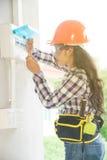 A verificação fêmea asiática do eletricista ou do coordenador ou inspeciona o interruptor do sistema bonde fotografia de stock royalty free