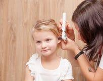 Verificação OTORRINOLARINGOLÓGICA da criança - orelha de exame do doutor de uma menina com oto imagens de stock