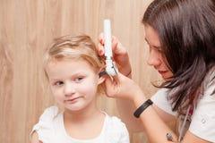 Verificação OTORRINOLARINGOLÓGICA da criança - orelha de exame do doutor de uma menina com oto imagem de stock royalty free