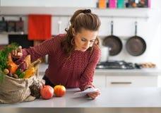 Verificações de exploração da dona de casa após compras na mercearia imagens de stock