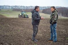 Verificações do agrônomo e do fazendeiro a umidade do solo antes do cer de sementeira imagem de stock