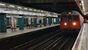 Verificações do passageiro uma programação estação de metro em Londres, Inglaterra fotos de stock royalty free