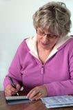 Verificación femenina mayor de la escritura Foto de archivo