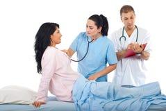 Verificación del doctor encima del paciente de la mujer en cama Imagen de archivo libre de regalías