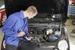 Verificación del mecánico principal un coche Imagen de archivo libre de regalías